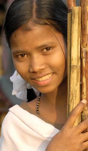 A girl holding bamboo and smiling - Worship in Adversity