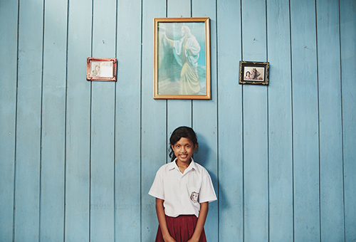 girl in a school uniform in front of a blue wall with framed pictures