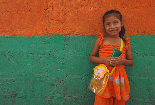 Girl in an orange dress smiling in front of an orange and green wall