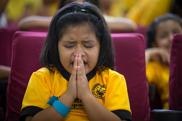A young girl prays