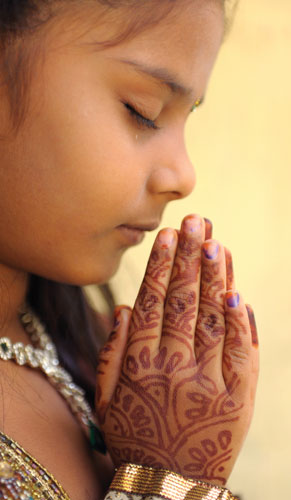 Girl praying with folded hands - World in Adversity