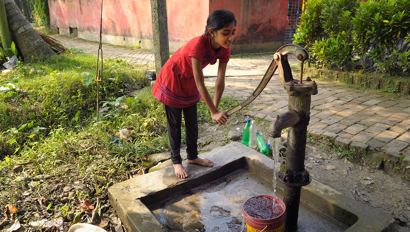 A girl pumping water