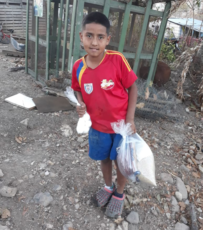a boy stands and smiles with a bag of goods