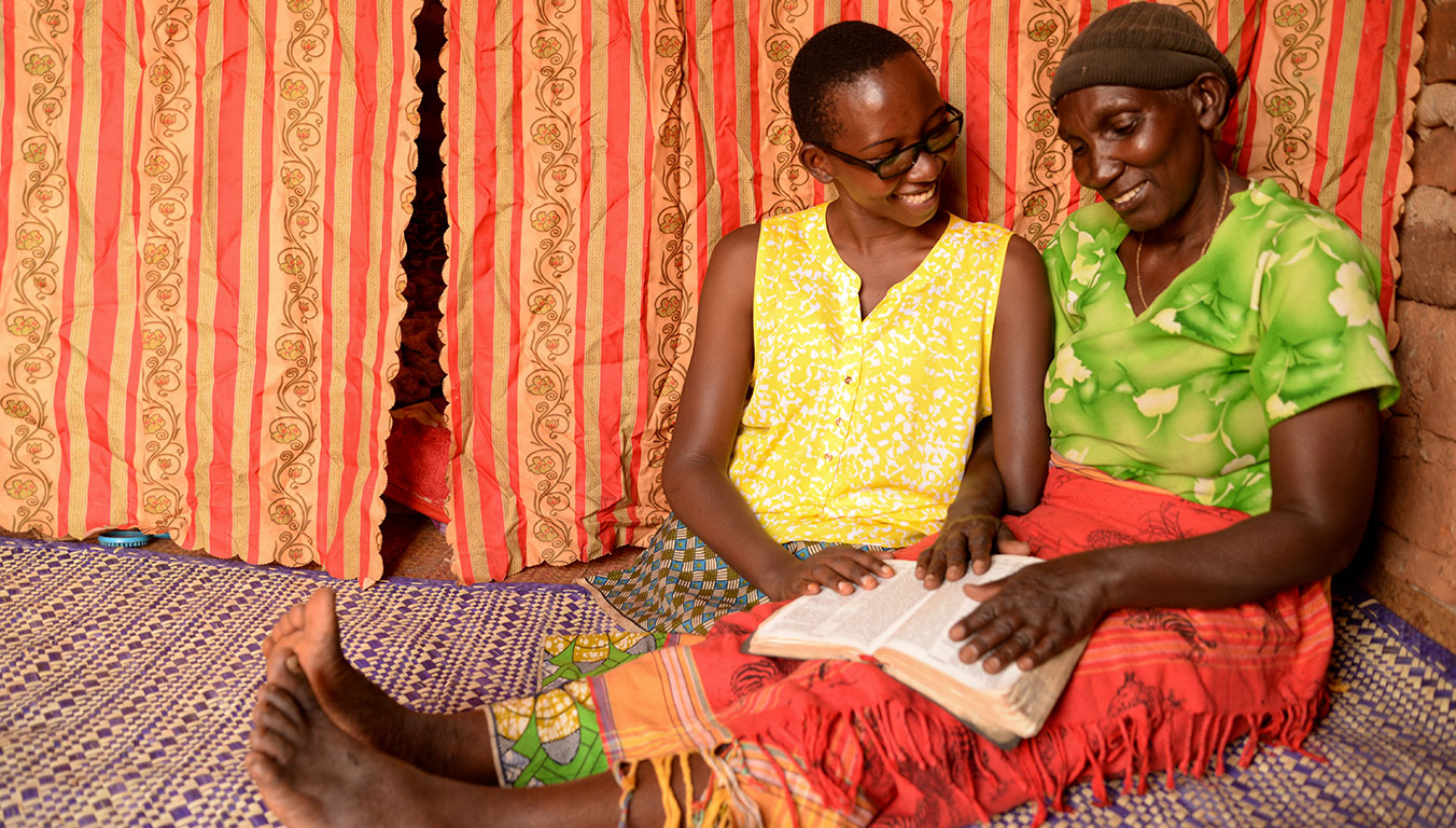 Grace and Birasasira read the Bible together in their Ugandan home