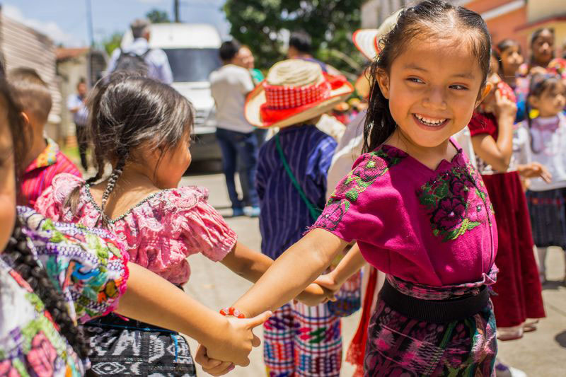 A group of little girls in traditional dresses hold hands as they spin around and smile