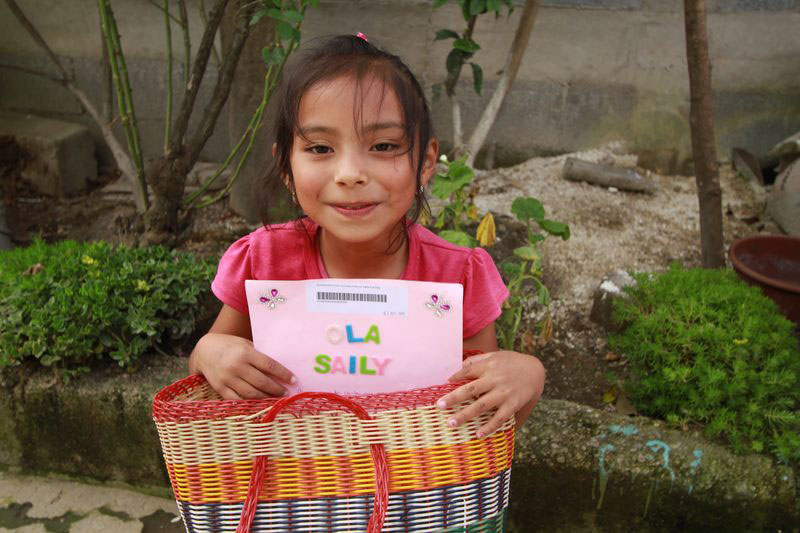 A young girl holds a letter from her sponsor