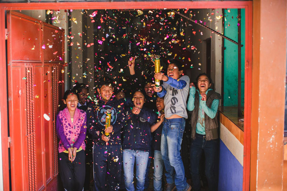A group of children celebrate the New Year by shooting confetti into the air