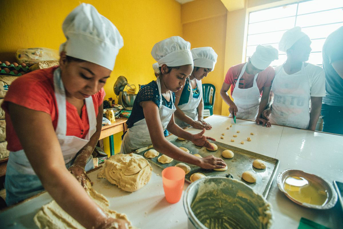 A group of children learn to bake as a part of a vocational training program