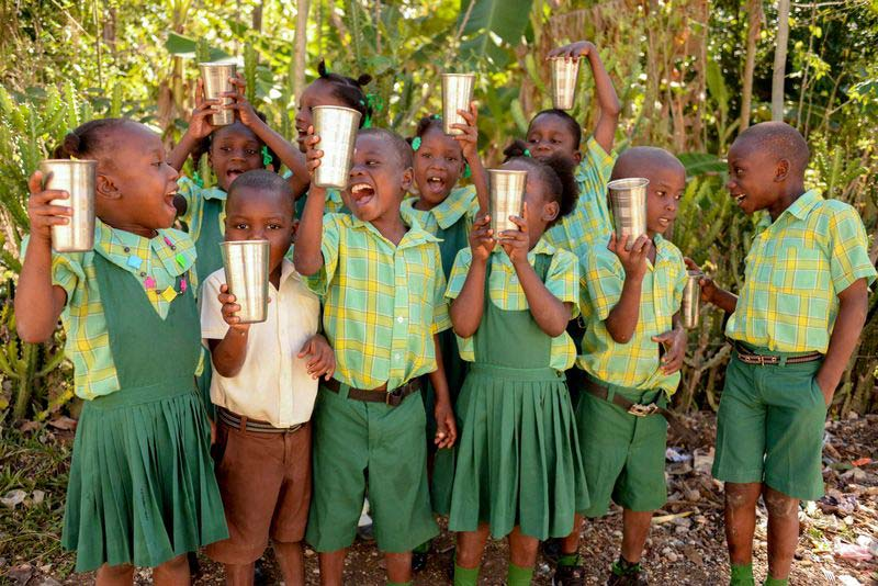 A group of children in a rural community smile and hold up glasses of clean water