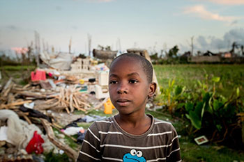a Haitian child stands in front of a home destroyed by Hurricane Matthew