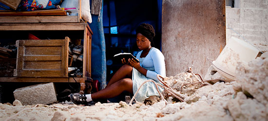 A Haitian college student sits amid the rubble of her home as she reads the Bible.