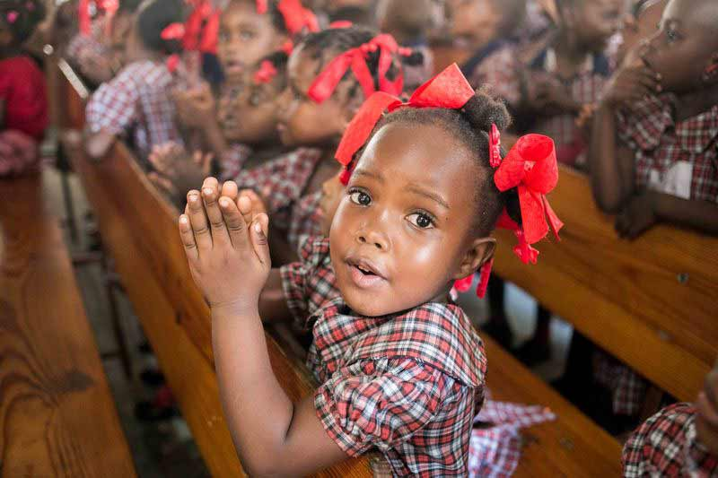 A young girl holds her hands together to pray
