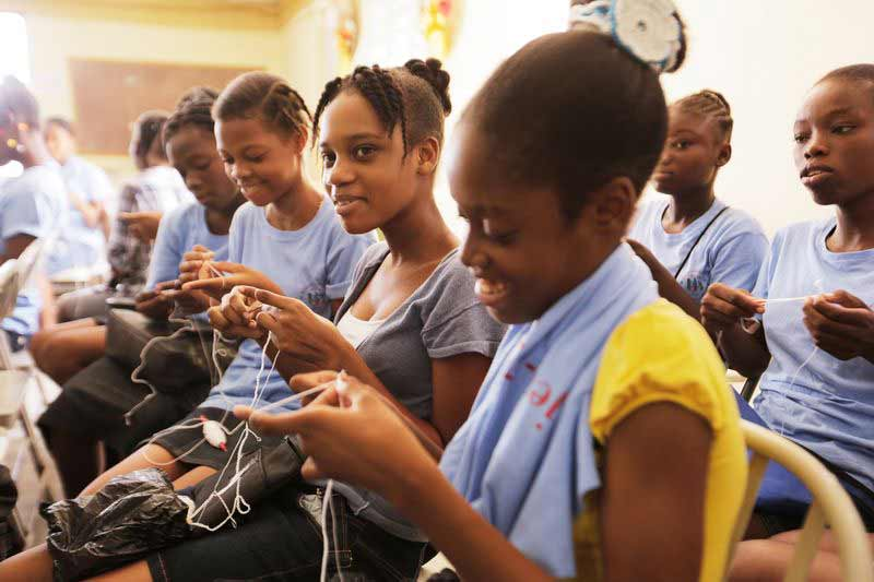 A group of young women learn vocational skills at their child development center