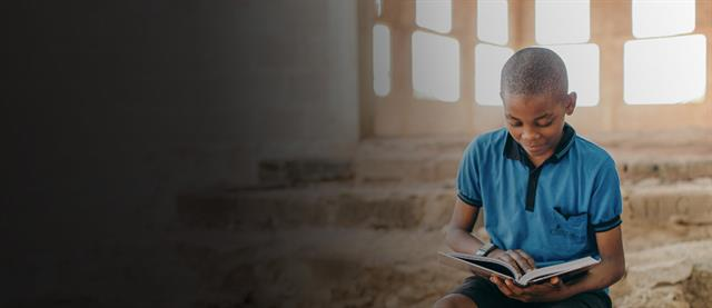Boy sitting and reading the bible