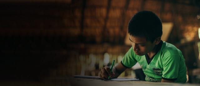 A boy living in Peru sits at a desk writing a letter