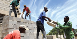 Haitian construction workers pass cinder blocks to one another.