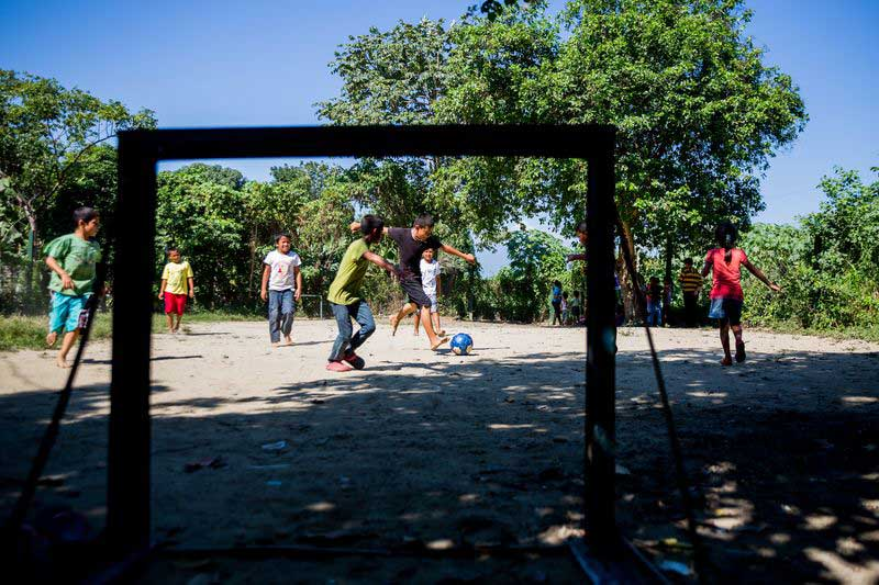 A group of boys play soccer at their child development center