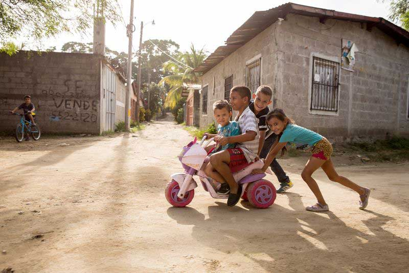 A group of children play together with a toy bicycle
