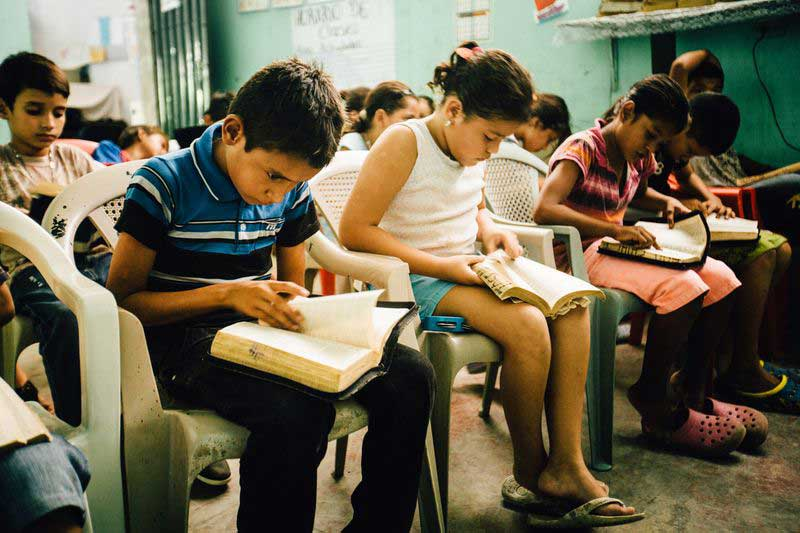Children sit in a classroom and read their Bibles together