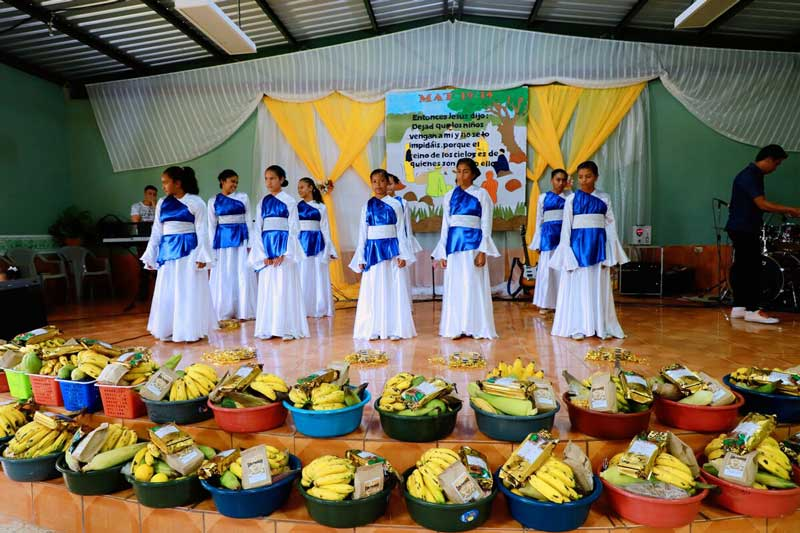 Teenage girls perform as a part of the First Fruits Feast at their church