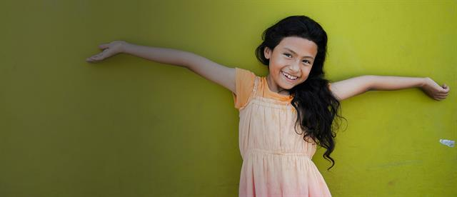 A girl stands in front of a greenish yellow all with her arms spread wide