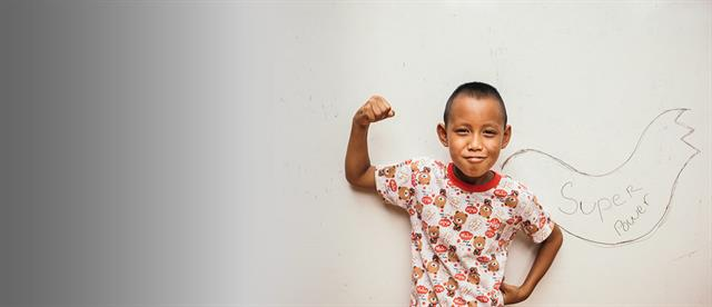 A young boy flexing his bicep with the words super power written out on a board behind him
