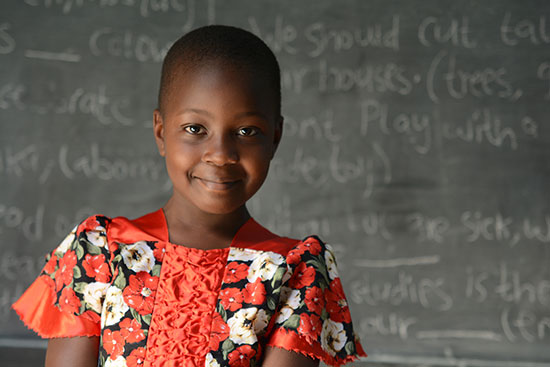 A Kenyan girl stands in front of a chalkboard with letters written on it