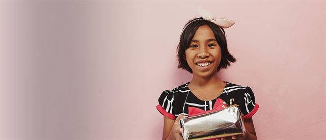 A smiling girl holding a book stands in front of a pink wall