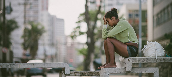 A girl sits on a concrete table in a city park