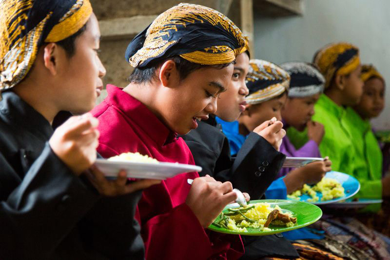 A group of children wearing traditional Indonesian dress have lunch together