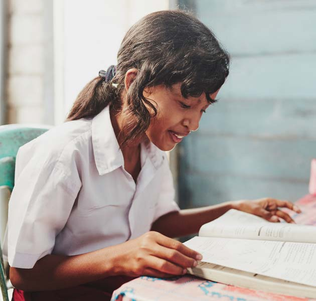 A girl reading a book in her school