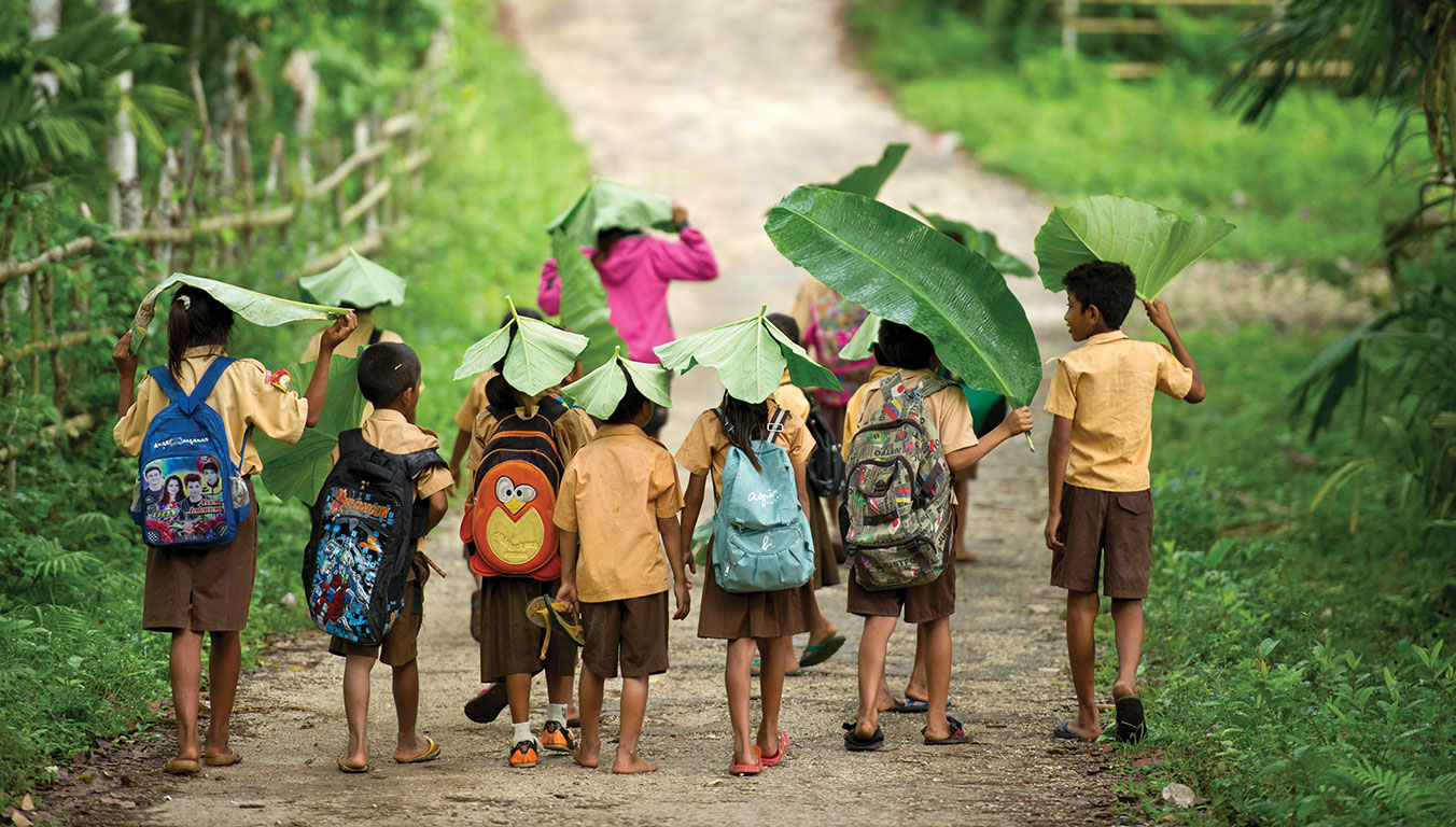 Children walking to school while covering their heads