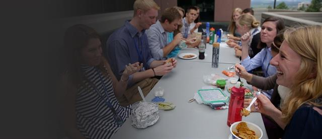 A group of interns eat together at a table
