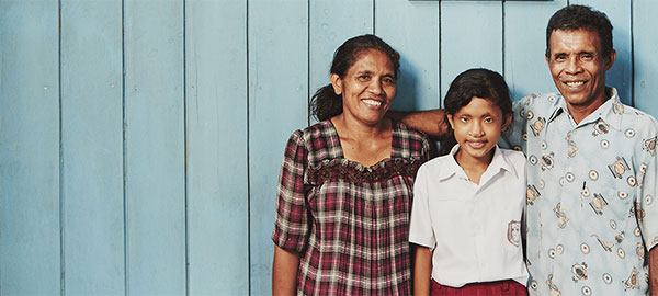 A mother, father and daughter stand in front of a blue wall with three pictures hanging on it.
