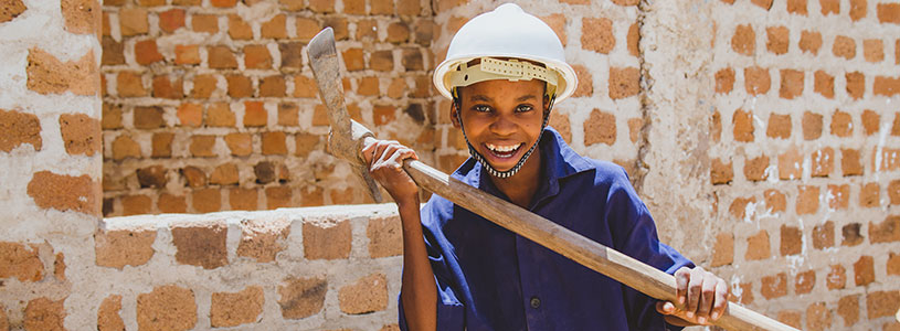 A smiling Tanzanian boy wearing a white construction helmet and holding a pick axe.