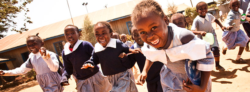 A group of young Kenyan school girls run and laugh at recess.