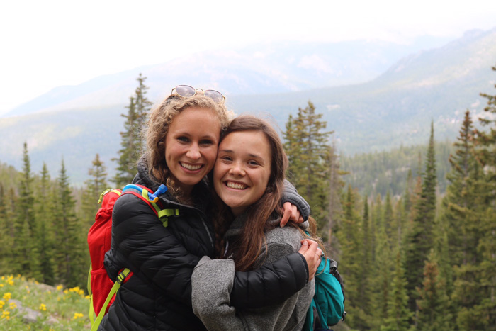 Two young ladies hug and smile with mountains behind them