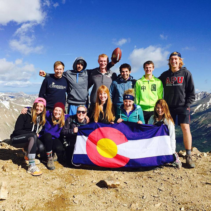A group of interns holding a Colorado state flag on a mountain top