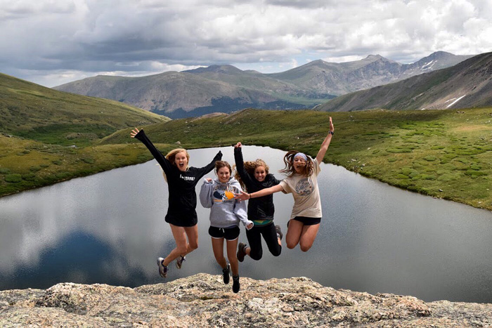 A group of young ladies jumping with mountains and a lake behind them