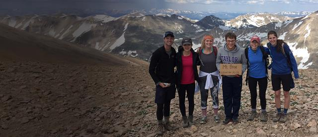 A group of interns on a mountaintop with areas of snow