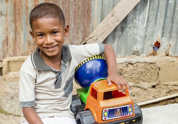 Jarwin smiles with his gift of a toy truck