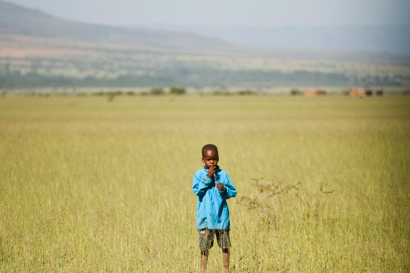 A young boy stands in a grassy field with mountains behind him
