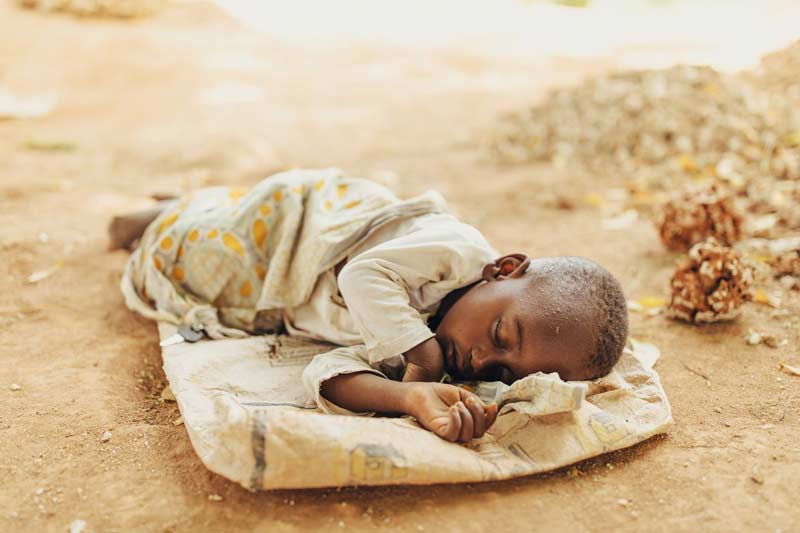 A young child sleeps peacefully on top of an empty burlap sack
