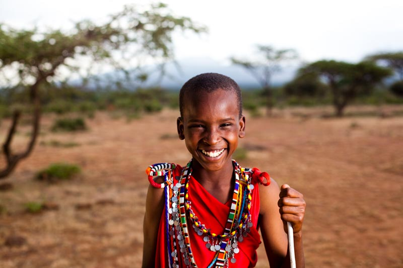 A young Masai boy smiles in the desert landscape of Kenya
