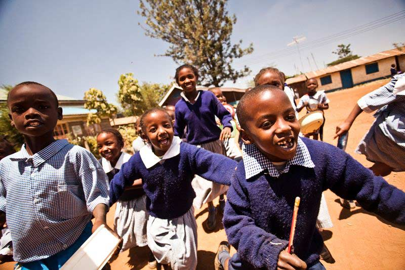 A group of children smile and run at their child development center
