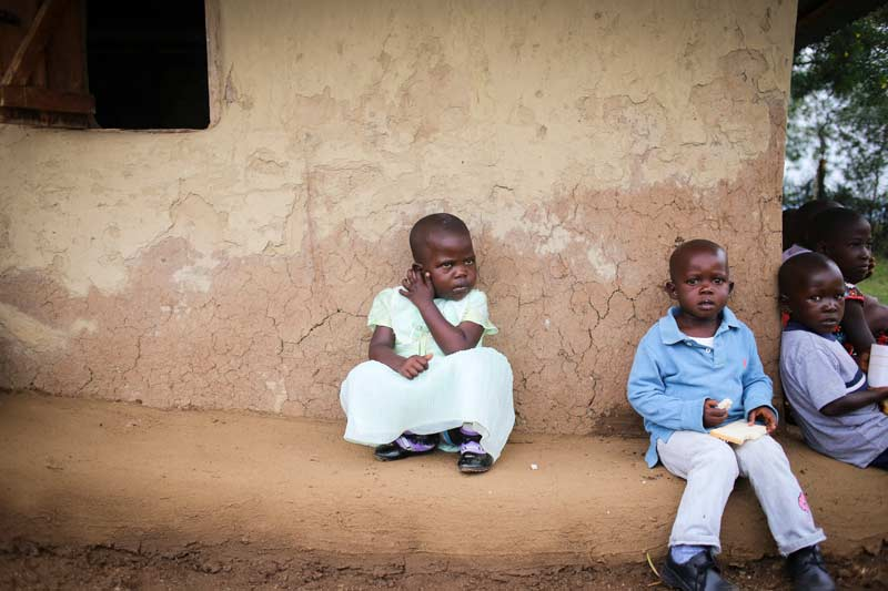 Children sit against the wall of a home