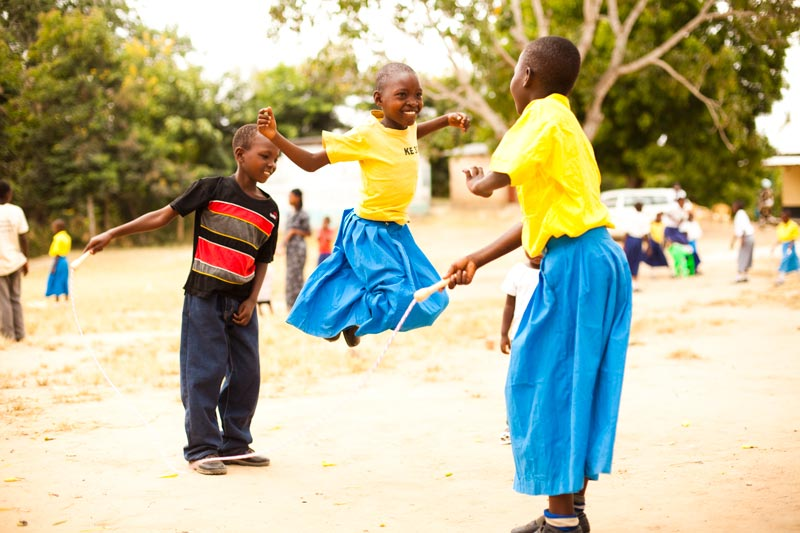 Children smile while playing jump rope at their child development center playground