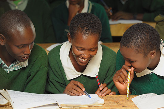 Three smiling Kenyan students smile while looking at a notebook.