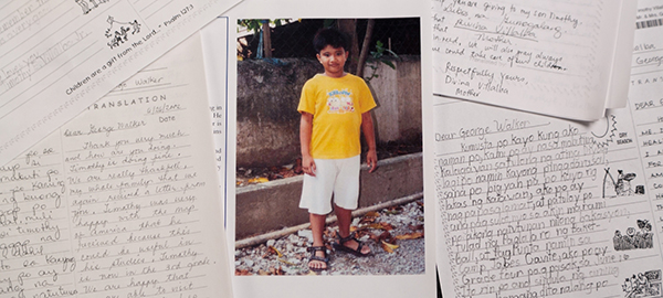 A picture of a sponsored child among several letters written to the child