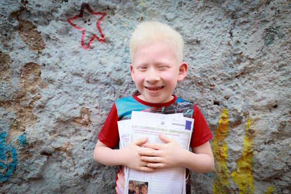 A boy smiles and holds a letter